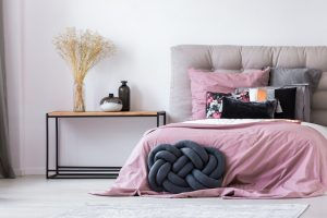 Pastel pink bedding on king size bed in cozy bedroom interior
