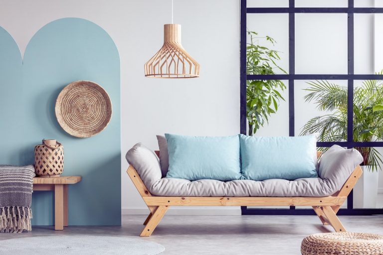 Urban jungle in bright white and blue living room interior with scandinavian futon sofa
